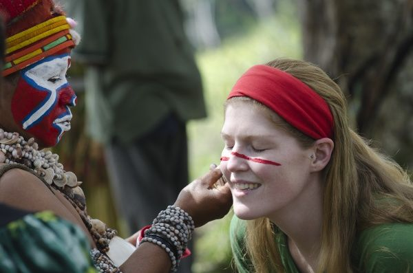 Tourist having her face painted at Sing-sing - The Paiya Show in Western Highlands Papua New Guinea